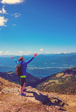woman standing on the top of a mountain with wonderful view to a lake