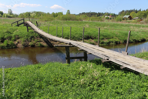 Old wooden bridge over river in summer countryside - 206589912