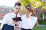 Young businesswoman showing tablet to businessman outdoors - 206594546