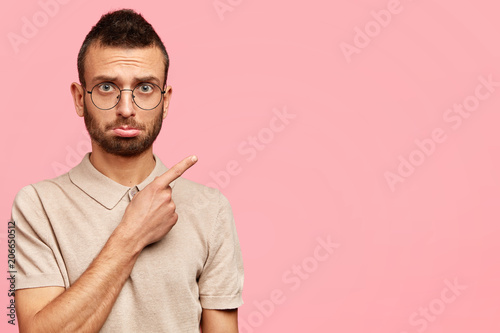 Worried displeased young male with trendy haircut, bristle, wears casual t shirt and round spectacles, indicates with fore finger at blank space, shows something scary, isolated on pink wall © Wayhome Studio