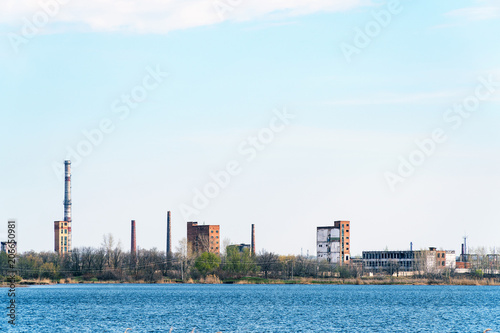 Fotobehang Gebouw in Puin Old Abandoned chemical factory with chimneys on the banks of the river