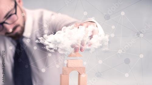 Leinwanddruck Bild Young handsome businessman using wooden building blocks behind cloud concept