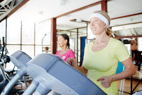 Poster Happy aged woman running on treadmill in sports center with her friend on background