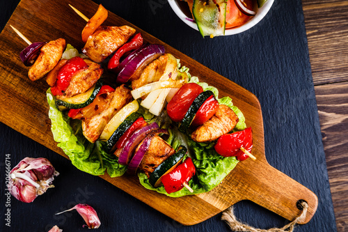 Kebabs - grilled meat with french fries and vegetables on wooden background - 206666714