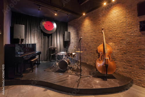 Modern jazz bar interior design, stage with black piano and cello
