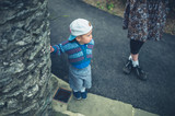 Little boy and his mother by a wall outside - 206675714