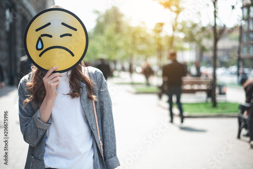 Lady Is Standing In The Street And Hiding Face Behind Upset Emoticon