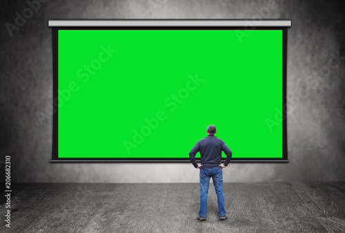 Man stands in front of big empty green screen - 206682310