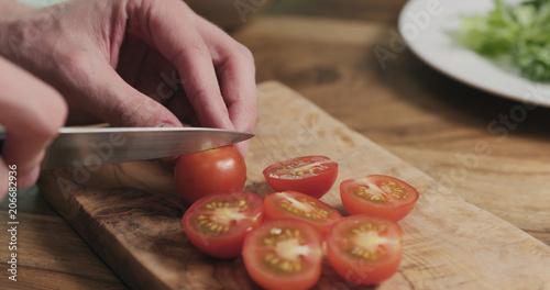 Fotobehang Kersen man hands slicing cherry tomato on wooden board