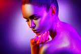 Fashion model woman in colorful bright sparkles and neon lights posing in studio, portrait of beautiful sexy girl. Art design colorful vivid makeup - 206691706