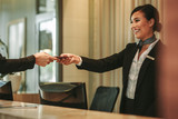 Smiling receptionist attending hotel guest - 206693509