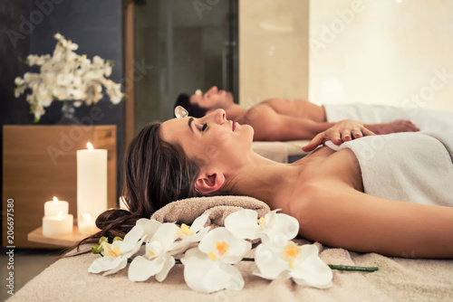 Leinwanddruck Bild Young man relaxing with his partner on massage beds at modern spa and wellness center