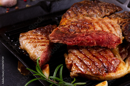 Grilled cut of beef steak in pan with spices on dark stone background