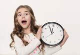 Excited little girl with clock at white background - 206709161