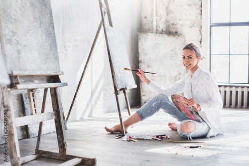 Female artist working on painting In bright daylight studio.