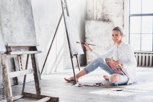 Foto Murales Female artist working on painting In bright daylight studio.