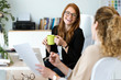 Two pretty young business woman relaxing one moment while drinking coffee in the office. - 206728706