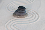 Pyramids of gray zen stones on light sand. Concept of harmony, balance and meditation, spa, massage, relax