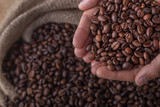 Hands on a sack of coffee beans - 206731785