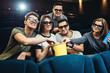Happy friends watching movie in cinema