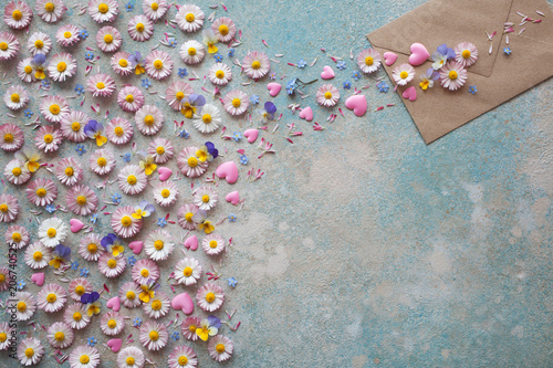 Flowers of daisies, pansies, pink hearts, forget-me-nots and an envelope on a colored background