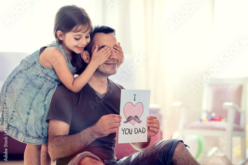 Happy Father's Day Concept. Child Daughter Hiding Surprise Postcard Present for Her Dad. - 206746938