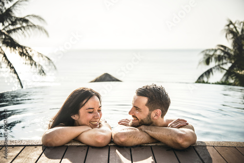 Leinwanddruck Bild Couple relaxing in a swimming pool