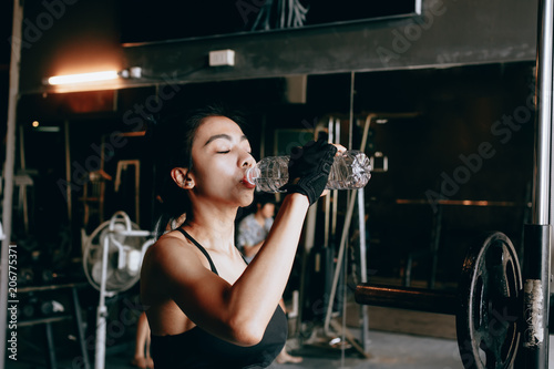 Poster Asian young woman drinking water in the gym.