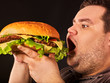 Diet failure of fat man eating fast food hamberger. Happy smile overweight person who spoiled healthy food by eating huge hamburger on fork. Junk meal leads to obesity. Expensive fast food restaurant.