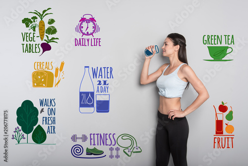 Zdrowy tryb życia. Rozochocona młoda kobieta prowadzi zdrowy styl życia i pije świeżą wodę w sportswear