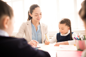 Schoolgirl studying together with teacher at the table at classroom