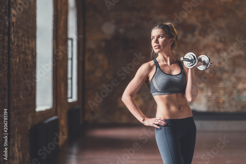 Poster Young sporty woman with a dumbbell in training
