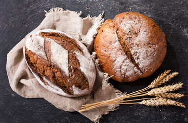 Fresh bread with wheat ears, top view
