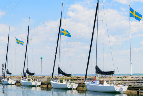 Four identical sailboats tied to a pier with three Swedish flags moving in the wind behind. Logos and id removed.
