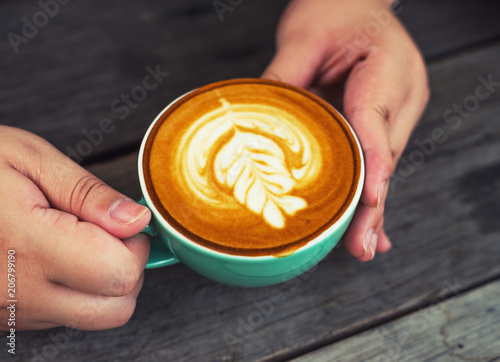 Hand women with cappuccino coffee in a green cup on wooden