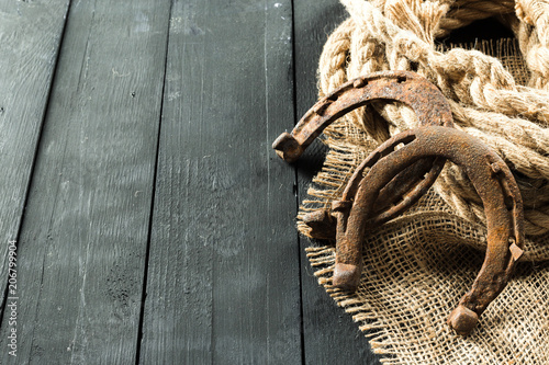 Old horseshoe and rope on wooden boards