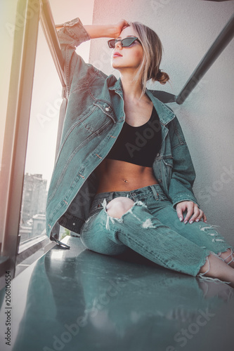 Young redhead girl in jeans clothes and sunglasses sitting on balcony alone.