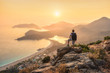Leinwanddruck Bild - Young sporty man with backpack standing on the top of rock and looking at the seashore and mountains at sunset in summer. Scene with man, sea, mountain ridges and orange sky with sun. Oludeniz, Turkey