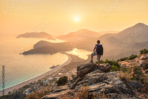 Leinwanddruck Bild Young sporty man with backpack standing on the top of rock and looking at the seashore and mountains at sunset in summer. Scene with man, sea, mountain ridges and orange sky with sun. Oludeniz, Turkey