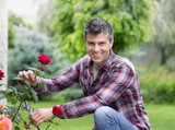 Gardener with scissors and red rose - 206852388
