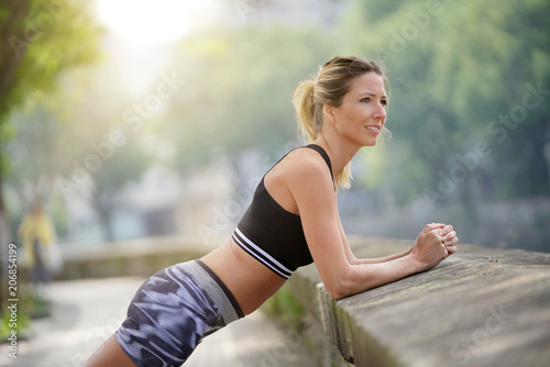Poster Athletic woman stretching out after running