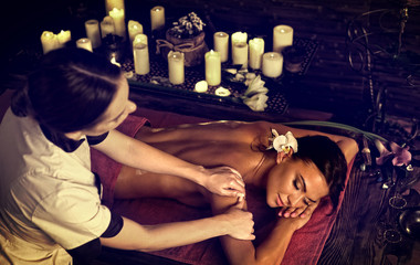 Massage of woman in spa salon. Girl on candles background treats problem back. Relaxation for benefit of beauty and health. Crop of bare back has relax. Alternative medicine in exotic therapy. © Gennadiy Poznyakov