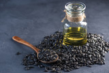 Sunflower seeds in a pile with spoon and golden oil in a glass bottle on the table. Healthy diet with vegetable fats.