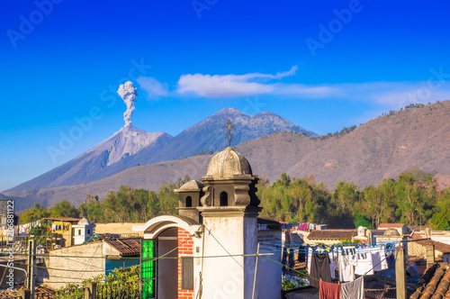 Fotobehang Donkerblauw Beautiful landscape of huge mountain in process of aruption with a column of ash, view from the rooftops of the building in Antigua city in gorgeous sunny day and blue sky