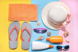 Beach accessories. Various creams, glasses, hat and towel with sea shells on a colored background. Top view. Flat Lay. - 206882582