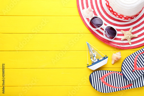 Leinwanddruck Bild Beach accessories with seashells and decorative ship on wooden table