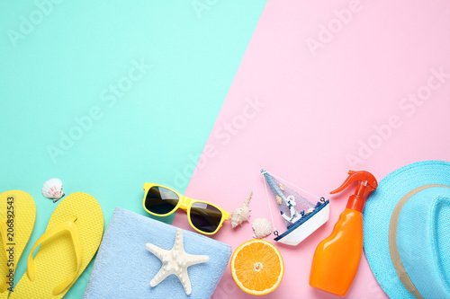 Fototapeta Summer accessories withdecorative ship and orange fruit on colorful background