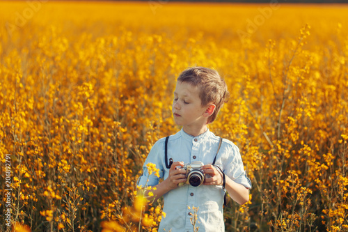 Leinwanddruck Bild Portrait of little boy photographer with camera on sunset yellow field background