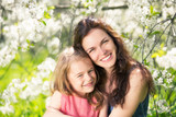 Mother and daughter in spring cherry blossom park - 206895976