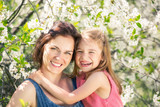Mother and daughter in spring cherry blossom park - 206896102